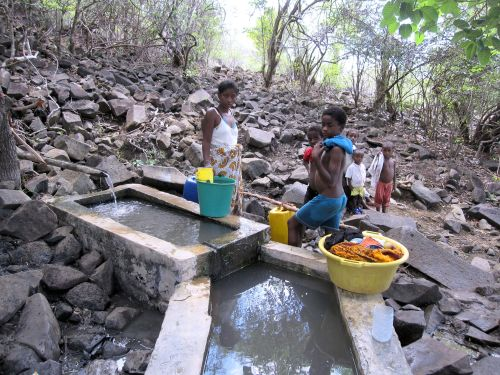 Still northern Madagascar, west coast. This is the water collection system. Natural filtration from the hills and about 1 km from the village. Washing clothes in the  cement pens and drinking water direct from the half bamboo pipe. Women's work. The boys are out fishing.